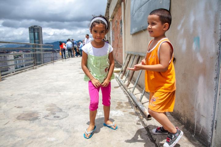 Niños juegan en la terraza del piso 27 de la Torre de David, protegidos por una endeble baranda