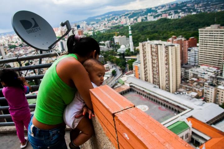 Una mujer asoma su bebé por la terraza desde el piso 27 de la Torre de David