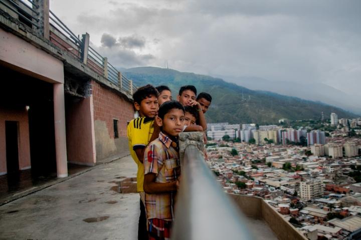 Niños juegan y posan en la baranda del piso 27 de la Torre de David