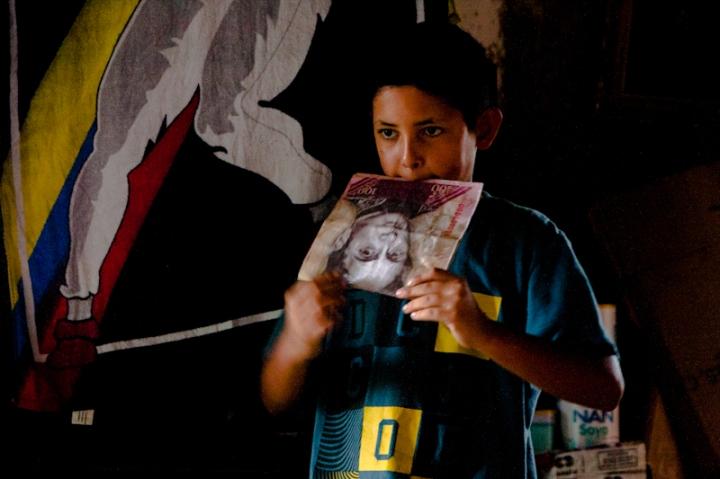 Un niño juega con un billete gigante mientras espera la hora de desalojar la Torre de David