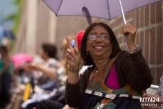 Una señora saluda desde la fila preferencial para personas de la tercera edad en Plaza Venezuela, a la espera de validar su firma para activar el Revocatorio