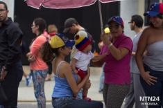 Una abuela, con su hija y nieta, esperan para validar su firma en Valencia