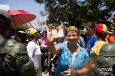 Una señora está a punto de pasar al centro de validación del CNE en Maracaibo, luego de 6 horas de cola y bajo una sensación térmica de 50 grados