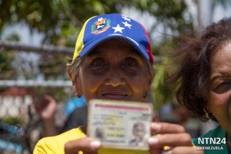 Una mujer anciana muestra su cédula antes de entrar a validar su firma en el centro del CNE en Maracaibo