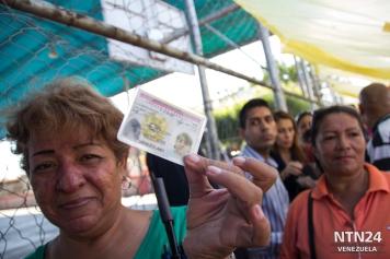 Una anciana muestra su cédula mientras está a punto de validar su firma para el Revocatorio en Cabimas, estado Zulia