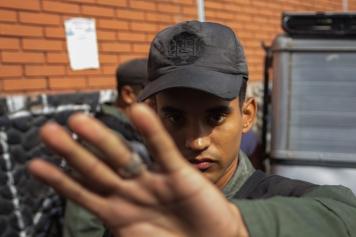 Un militar intenta impedir una fotografía mientras otro funcionario golpea a un presunto ladrón que fue capturado en la cola para la validación en Plaza Venezuela, Caracas, el 24 de junio.