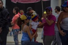 Una familia bromea en la fila para validar su firma en Valencia, estado Carabobo, el 21 de junio.