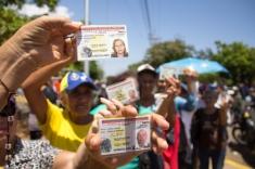 Un grupo de mujeres de la tercera edad levantan su cédula para exigir su derecho a validar su firma en miras al Revocatorio. Han cumplido para el momento de la foto 8 horas de cola bajo una sensación térmica de 50 grados en Maracaibo, estado Zulia, el 22 de junio.