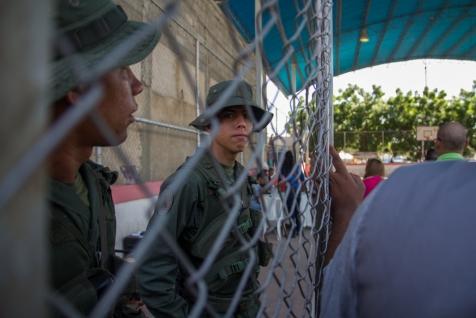 Un funcionario de la Guardia Nacional resguarda la fila de gente que busca validar su firma para el Revocatorio en Cabimas, estado Zulia, el 22 de junio.