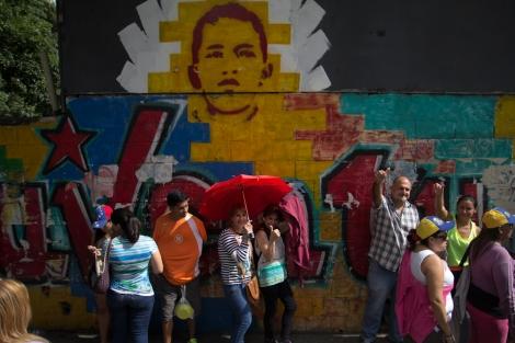 Una fila aguarda su turno para validar su firma, están frente a un mural de Hugo Chávez joven. Viernes 24 de junio