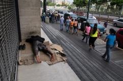 Una multitudinaria fila para validar la firma en miras al Revocatorio pasa al lado de un indigente en Plaza Venezuela. Viernes 24 de junio.