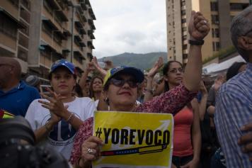 Una dama de la tercera edad mantiene en alto su entusiasmo, minutos después del cierre de la validación en Plaza Venezuela, Caracas, aun cuando no pudo validar su firma por la medida del CNE de dar cierre al proceso a las 4:00 p.m. independientemente de que hubiera gente en fila. Viernes 24 de junio.